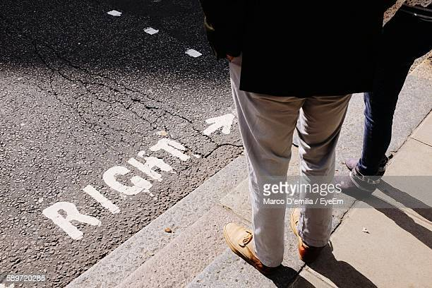 Low Section Of Man And Woman Standing On Footpath By Road Sign