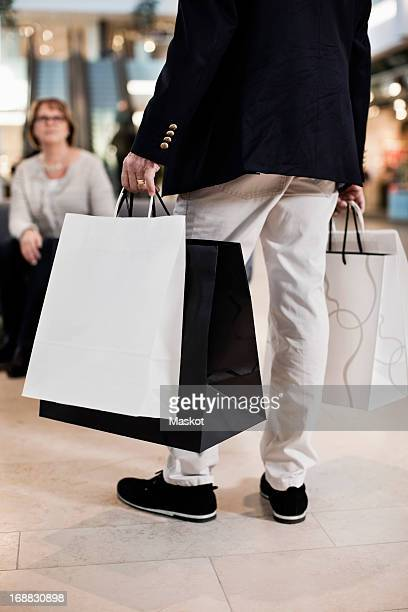 Low section of man carrying shopping bags with woman in background at mall