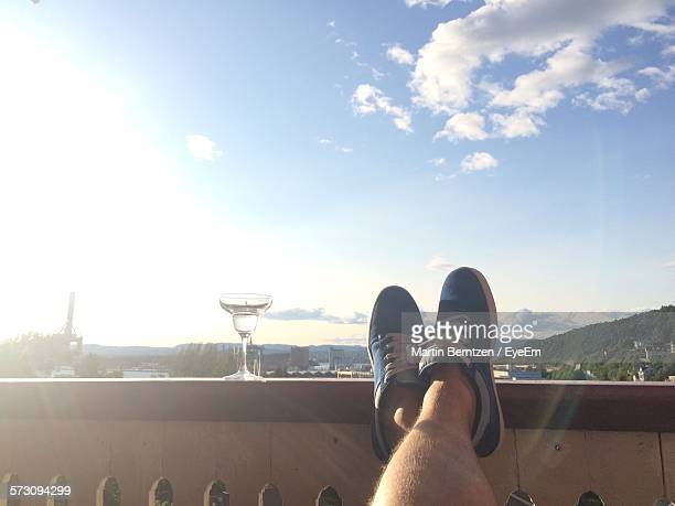 Low Section Of Man Feet On Railing With Martini Glass Against Sky