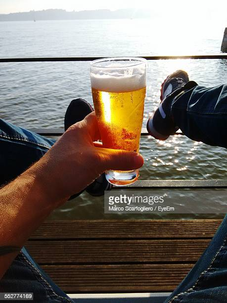 Low Section Of Man Holding Beer Glass While Sitting On Wooden Plank Over Sea