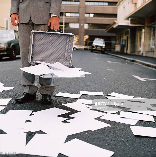 Low section of man holding opened briefcase with papers all around on road