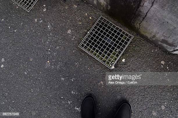 Low Section Of Man In Front Of Metal Grate On Sidewalk