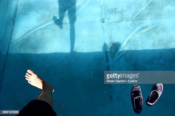Low section of man jumping in swimming pool