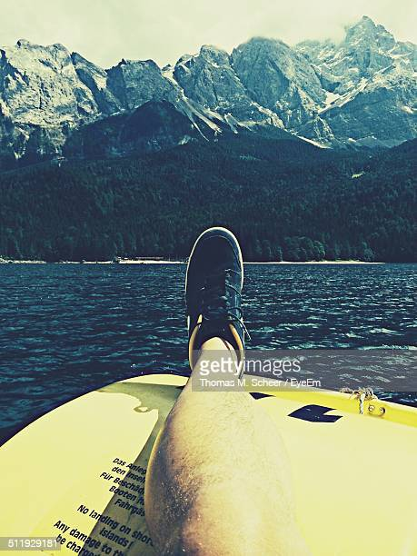 Low section of man on boat in river against mountains