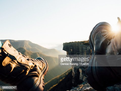 Low Section Of Man On Cliff Against Clear Sky