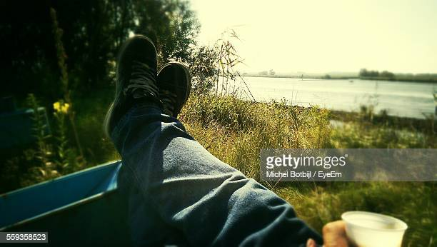 Low Section Of Man Relaxing In Park Near Lake