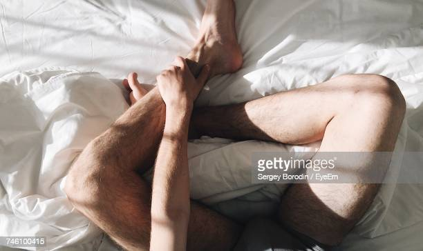 Low Section Of Man Relaxing On Bed At Home