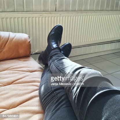 Low Section Of Man Relaxing On Couch