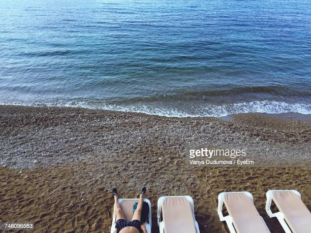 Low Section Of Man Relaxing On Lounger At Beach