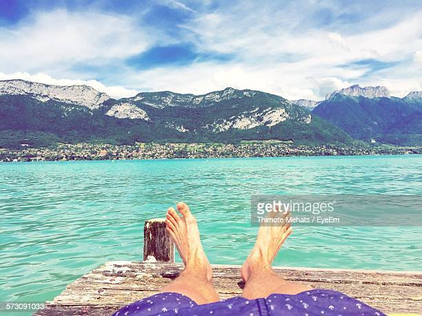 Low Section Of Man Relaxing On Pier Over Lake Against Sky