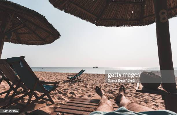Low Section Of Man Relaxing On Wooden Deck Chair At Beach Against Sky