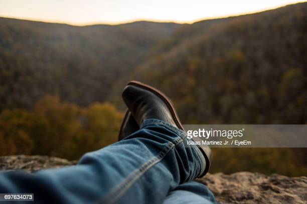 Low Section Of Man Resting Against Mountain