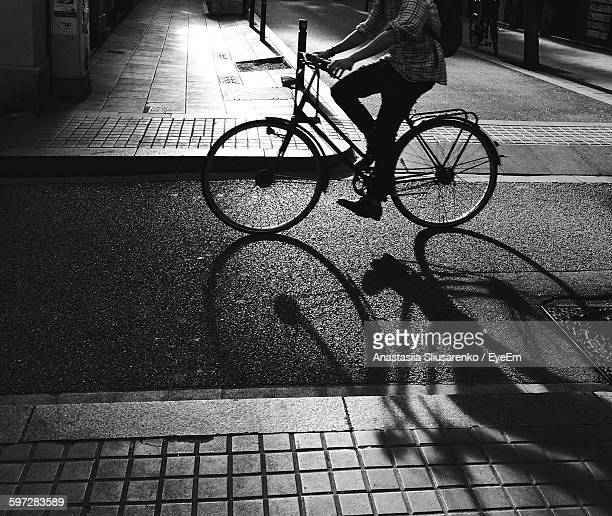 Low Section Of Man Riding Bicycle On Street At Night