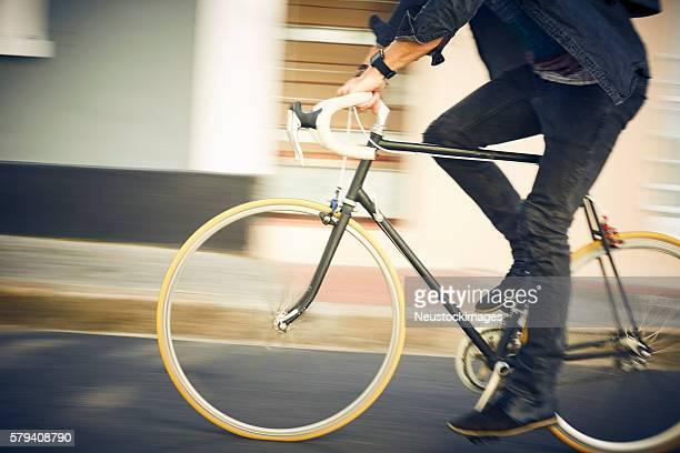 section basse de l'homme équitation un vélo dans la rue
