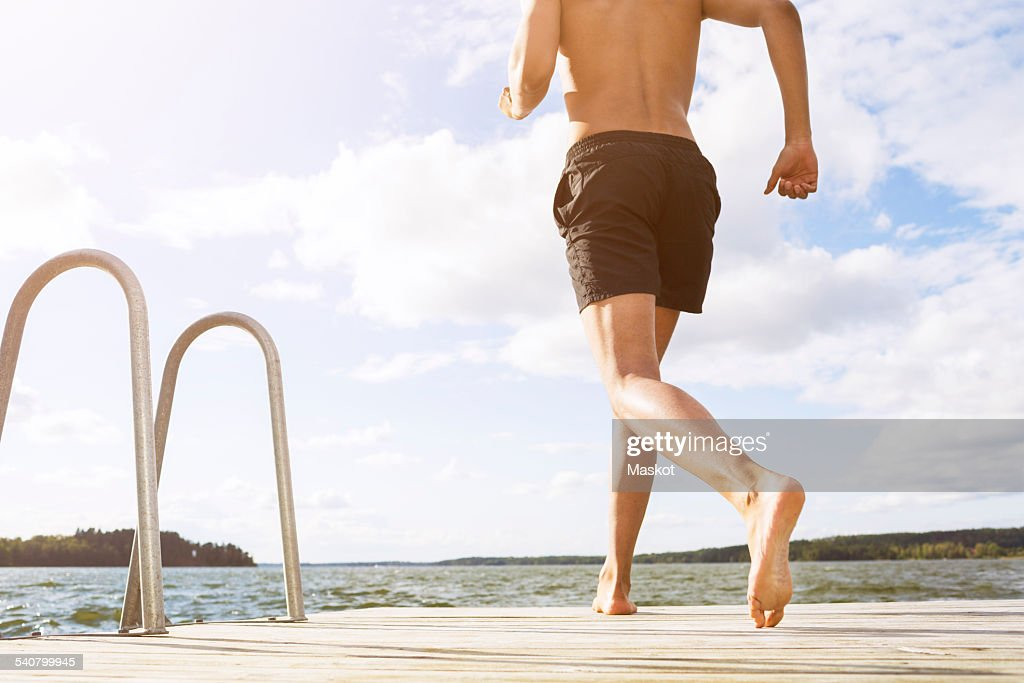 Low section of man running on boardwalk at lake