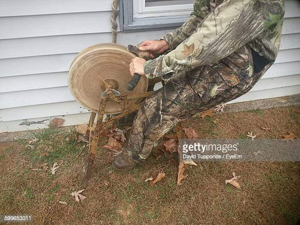 Low Section Of Man Sharpening Axe In Yard