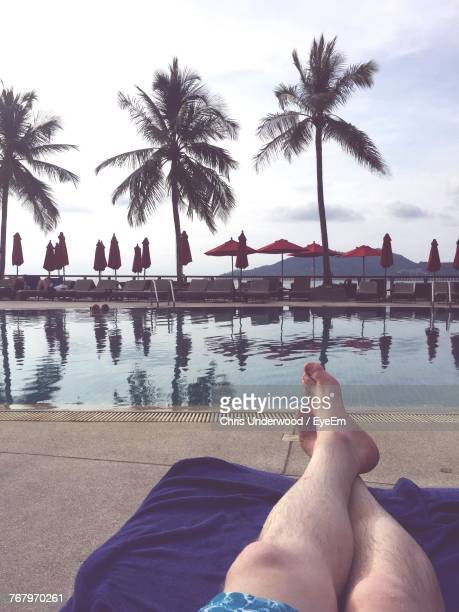 Low Section Of Man Sitting By Swimming Pool Against Sky