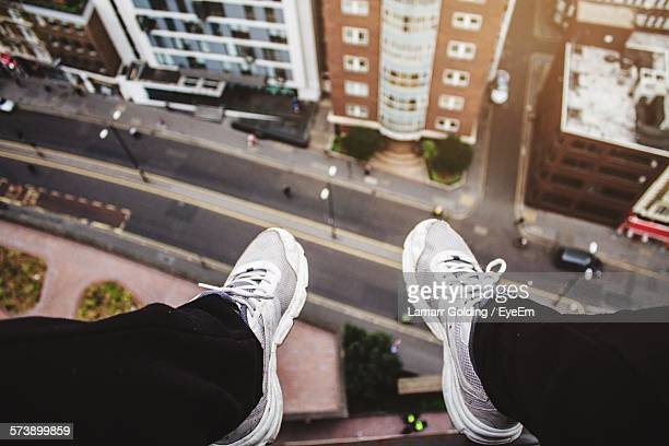 Low Section Of Man Sitting On Terrace Over Road In City