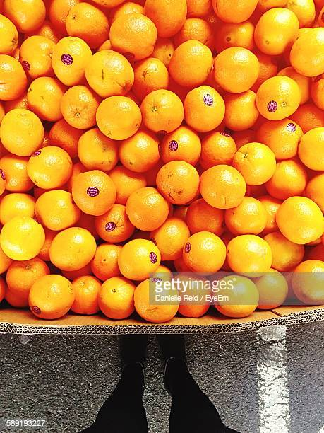 Low section of man standing against oranges for sale at market