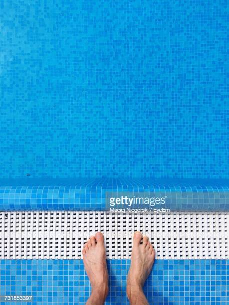 Low Section Of Man Standing At Poolside