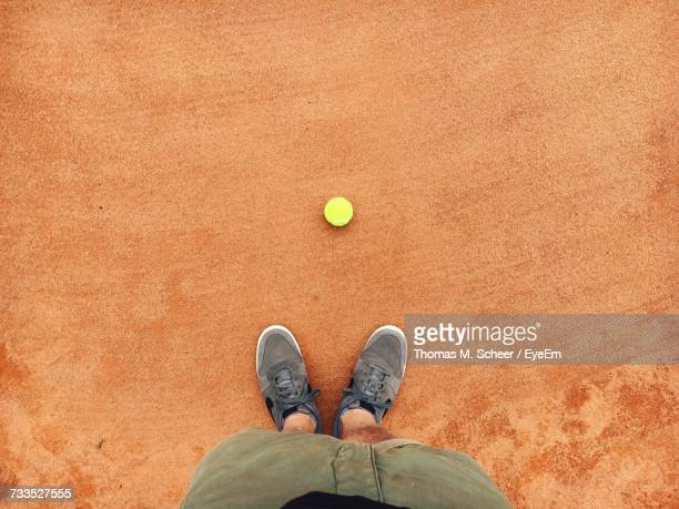 Low Section Of Man Standing By Ball At Tennis Court