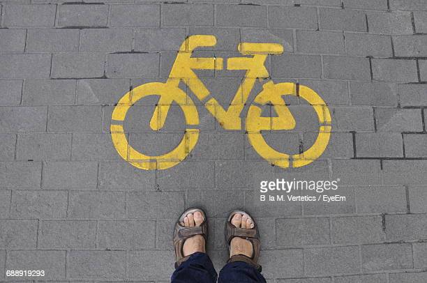 Low Section Of Man Standing By Bicycle Sign On Street