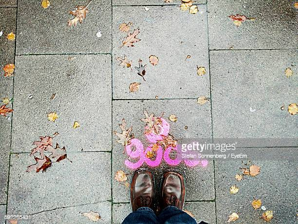 Low Section Of Man Standing By Pink Number On Wet Footpath