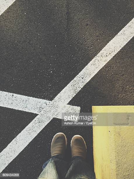 Low Section Of Man Standing By Road Markings On Street