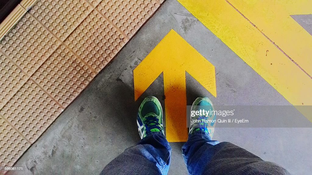 Low Section Of Man Standing By Yellow Arrow Sign