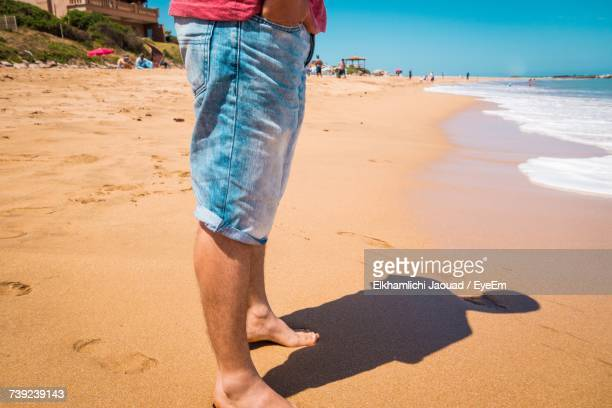 Low Section Of Man Standing On Beach
