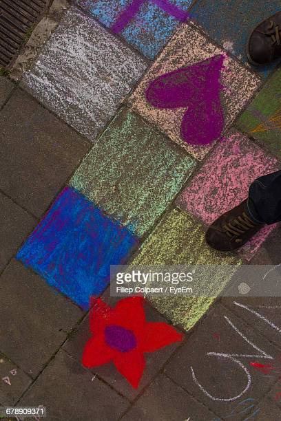 Low Section Of Man Standing On Chalk Drawing At Footpath