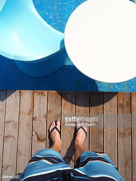 Low Section Of Man Standing On Deck By Poolside