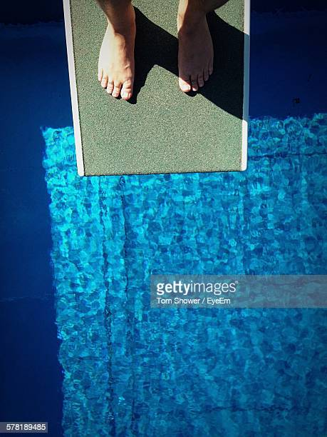 Low Section Of Man Standing On Diving Platform Over Swimming Pool