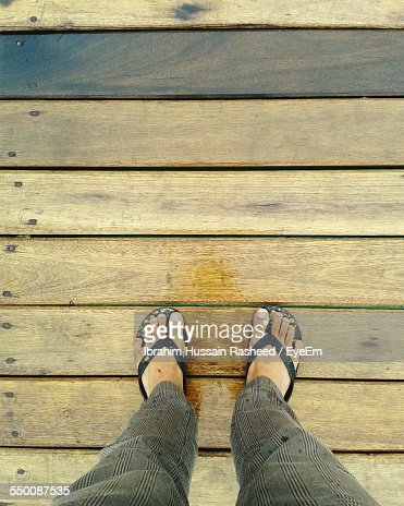 Low Section Of Man Standing On Floorboard