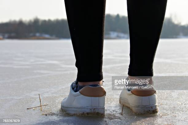 Low Section Of Man Standing On Frozen Lake