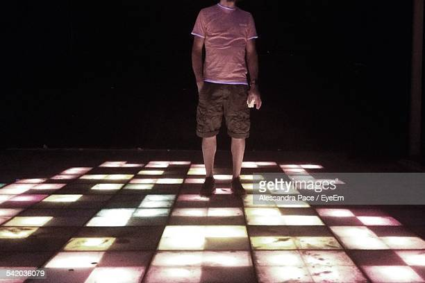 Low Section Of Man Standing On Illuminated Dance Floor At Night Club