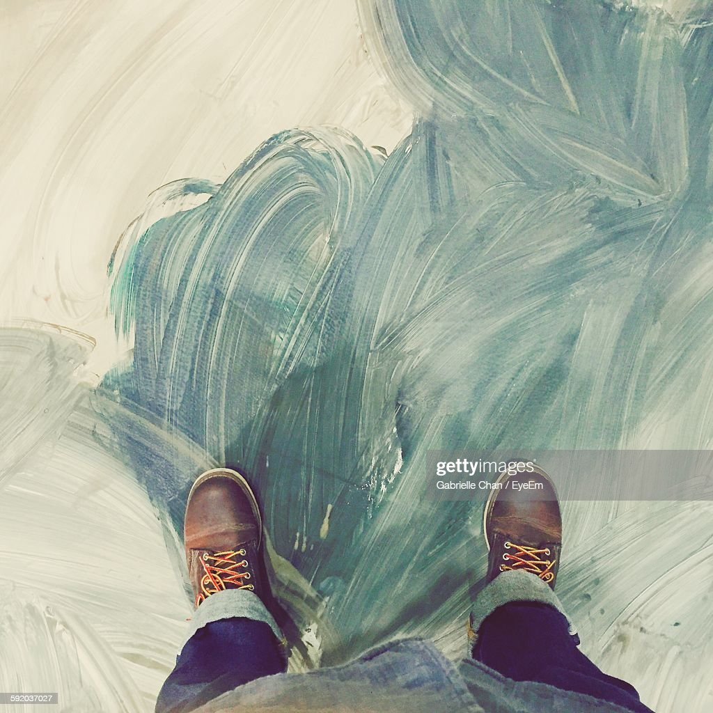 Low Section Of Man Standing On Painted Floor