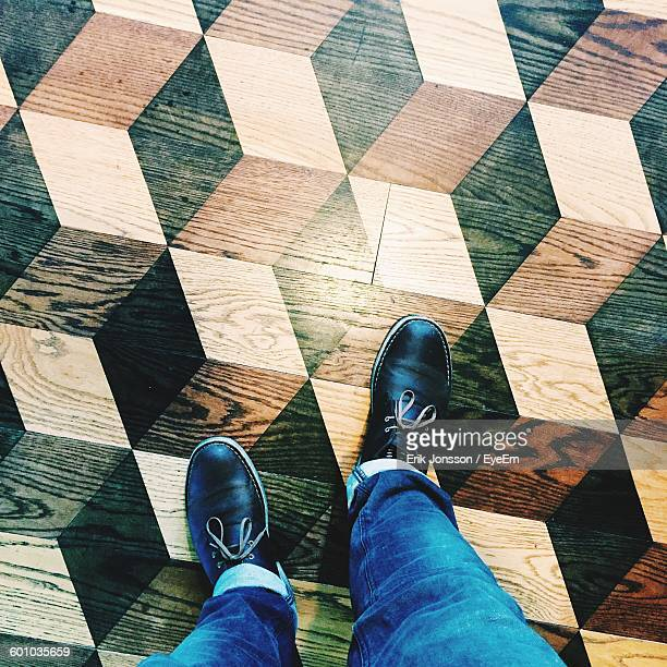 Low Section Of Man Standing On Pattern Hardwood Floor