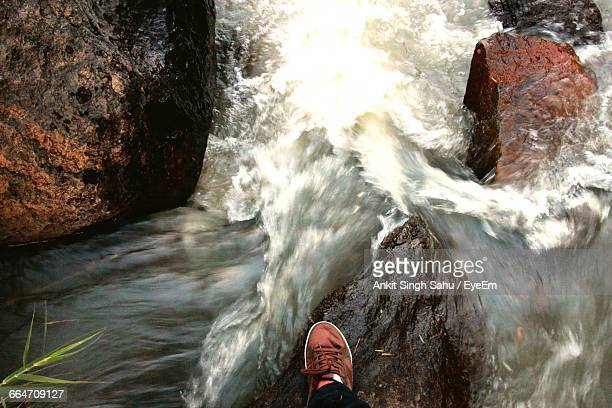 Low Section Of Man Standing On Rock In Front Of Waterfall