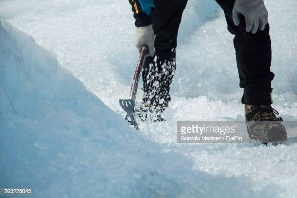 Low Section Of Man Striking Ice With Adze
