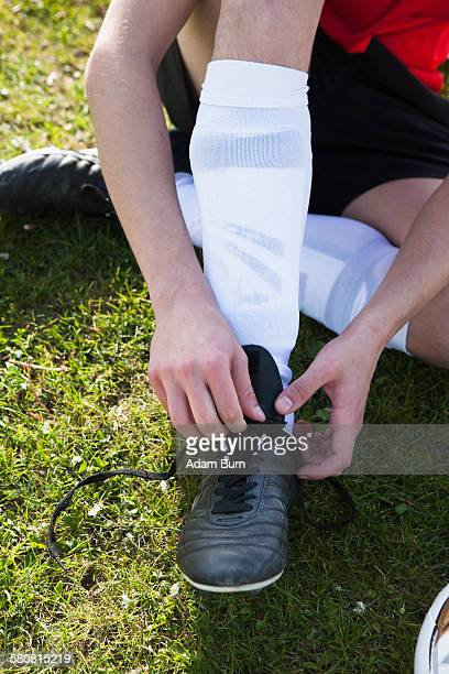 Low section of man tying soccer shoe on field