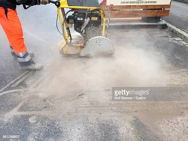 Low Section Of Man Using Machine On Road