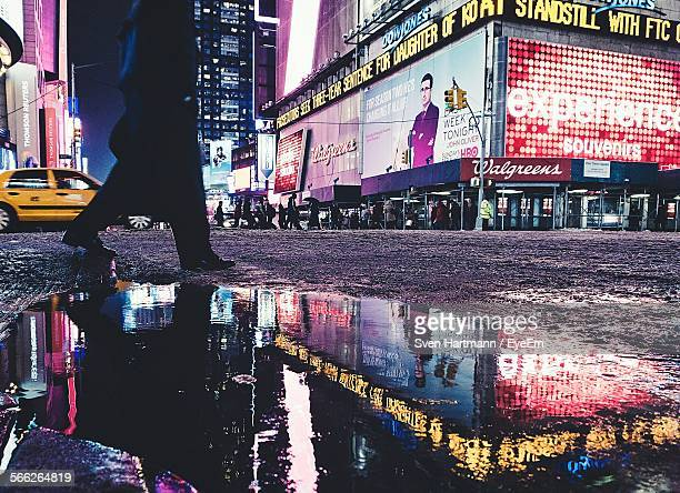 Low Section Of Man Walking By Puddle On Street