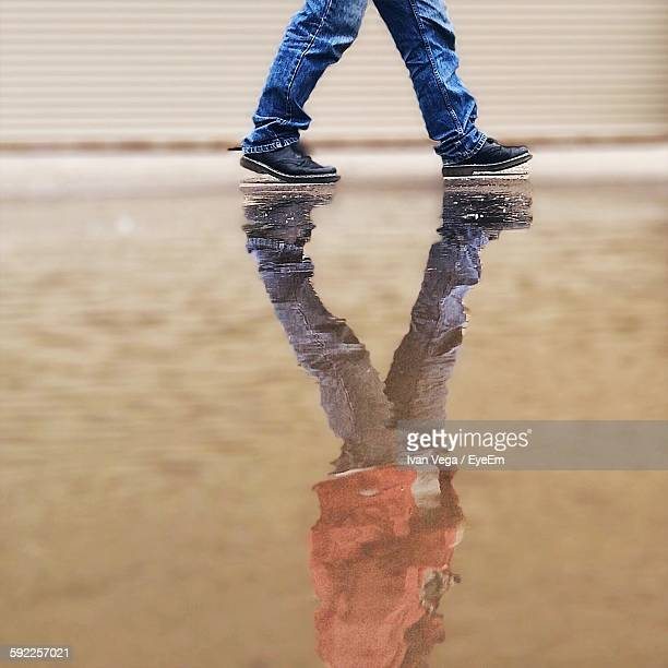 Low Section Of Man Walking By Puddle With Reflection At Street