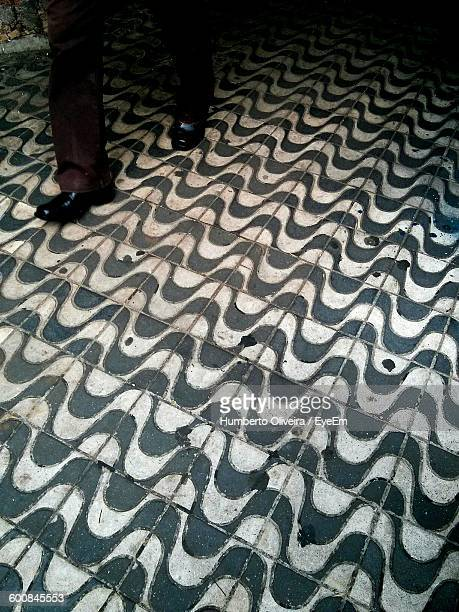 Low Section Of Man Walking On Patterned Floor