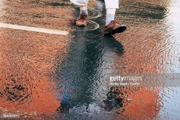 Low Section Of Man Walking On Wet Road
