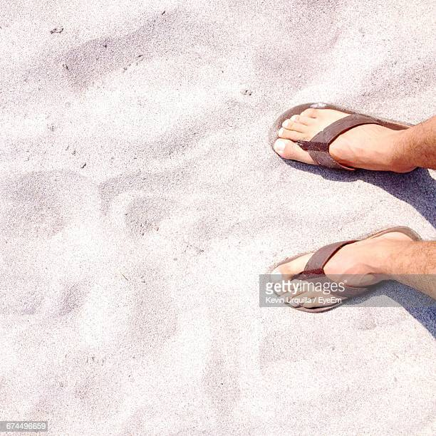 Low Section Of Man Wearing Flip-Flop Standing At Beach