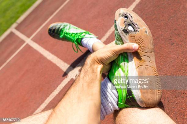 Low Section Of Man Wearing Shoes On Running Track