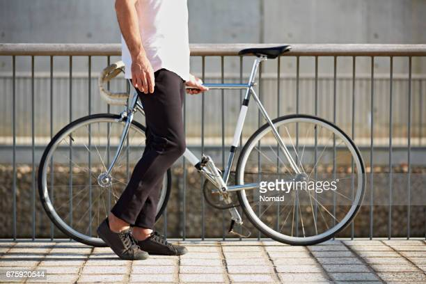 Low section of man with bicycle by railing