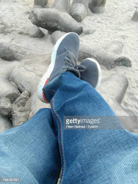 Low Section Of Man With Legs Crossed At Ankle Relaxing On Shore At Beach